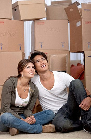 Couple portrait with boxes moving to a new home